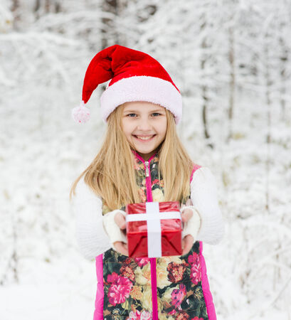 young girl with red hat holds out a gift photo