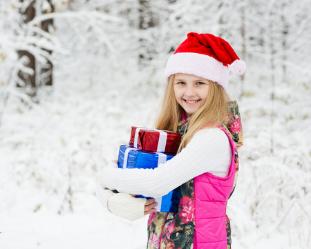 young girl with santa hat holding pile of gifts photo