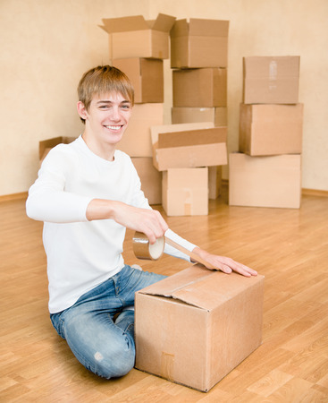 porter house: happy young man packs cardboard boxes for moving into a new home