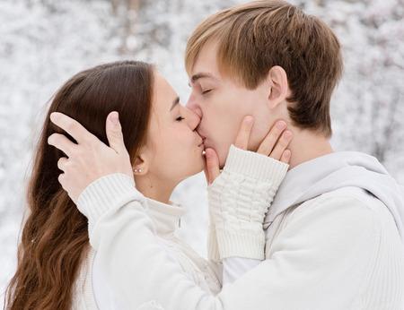 novios besandose: Joven pareja besándose en el bosque de invierno