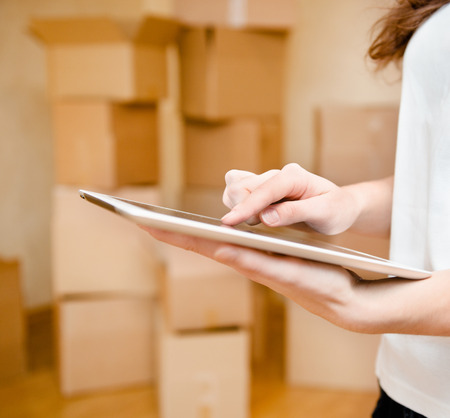 porter house: hand using tablet computer with cardboard boxes on background Stock Photo