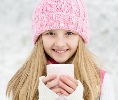 A young girl holding a cup of hot drink and smiling at the background of a winter forest photo