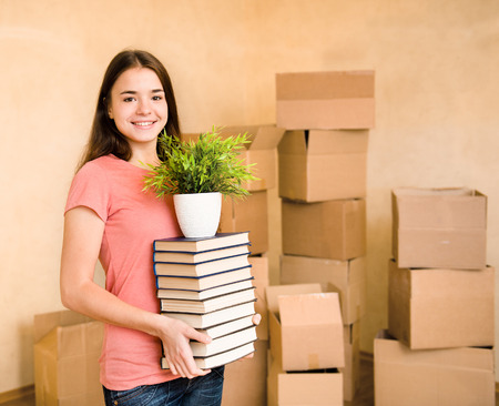 college dorm: Young woman moving house to college, holding pile books and plant