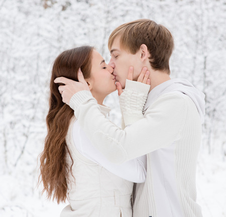 forehead: Young couple kissing in winter forest