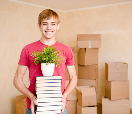 first move: Young boy moving house to college, holding pile books and plant