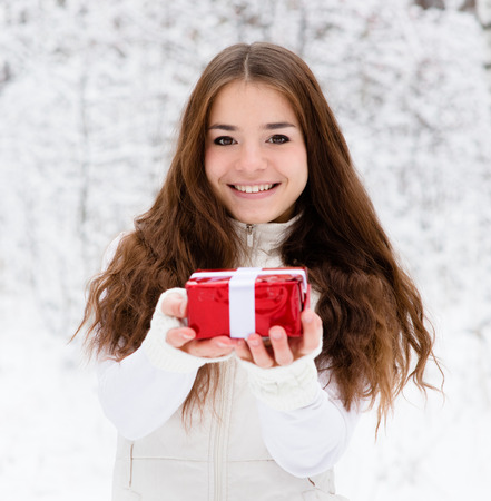 young girl with small red gift box standing in winter forest photo