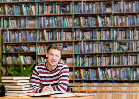 high: Smiling male student with open book working in a library