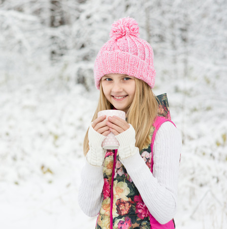 little girl holding a cup of hot drink and smiling at the background of a winter forest photo