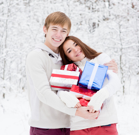 young couple hugging and holding gifts photo