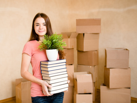 Teen girl moving house to college, holding pile books and plant Stock Photo