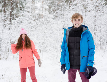 snowballs: happy young couple having fun together in snow in winter woodland throwing snowballs