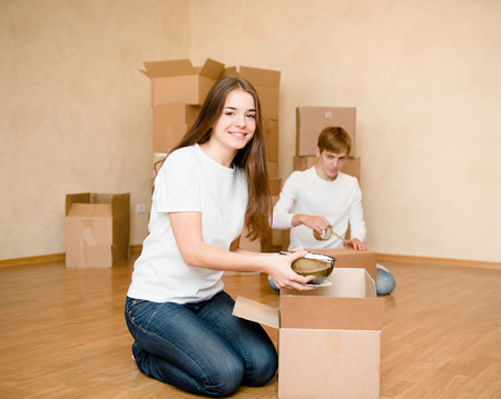college dorm: Young couple puts things in cardboard boxes for moving into a new home
