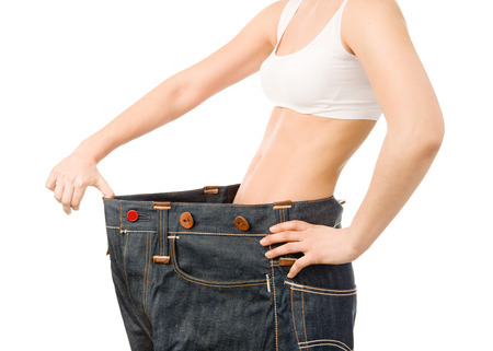 woman shows her weight loss by wearing an old jeans. isolated on white background