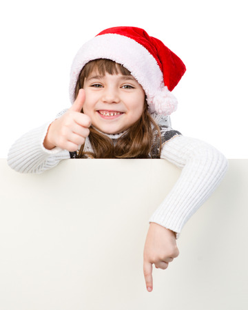 Beautiful young girl with santa hat standing behind white board . isolated on white background photo