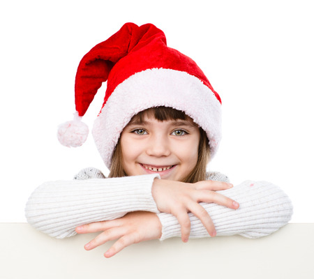 Christmas girl with santa hat behind white board looking at camera. isolated on white background photo