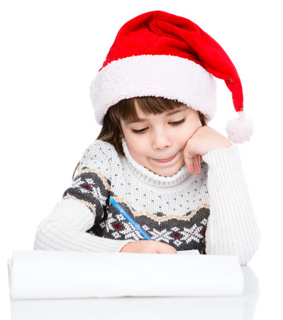 young girl in Santa hat writes letter to Santa photo