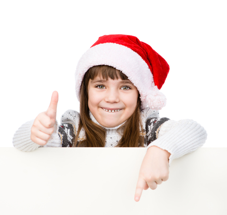 Beautiful young girl with santa hat standing behind white board. isolated on white background photo