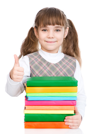 pile of books: happy small girl with pile books showing thumbs up. isolated on white background