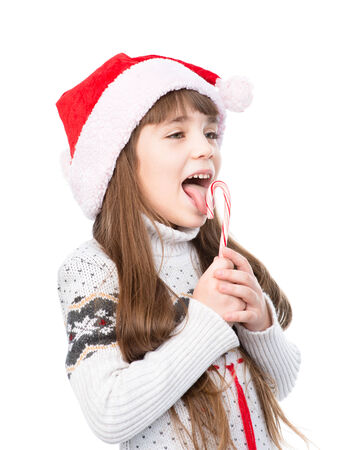 girl licking: happy girl in santa hat with Christmas candy cane. isolated on white background