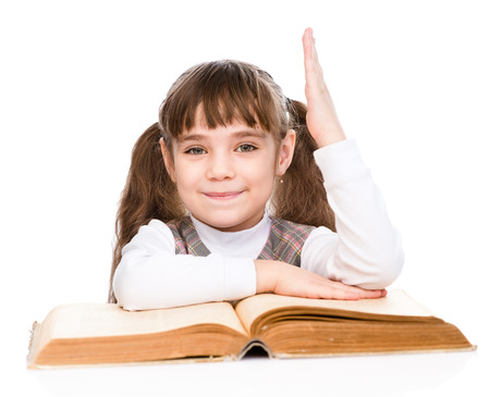 knowing: little girl with book raising hand knowing the answer to the question. isolated on white background Stock Photo
