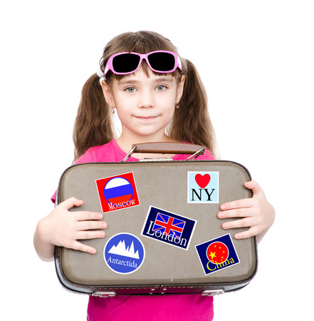 Young girl holding suitcase with stickers from various countries. isolated on white background photo