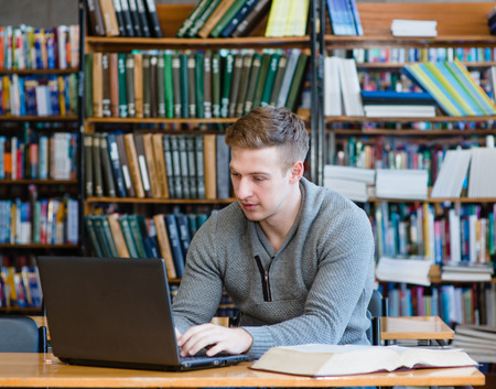 research study: Young male student using laptop in the university library