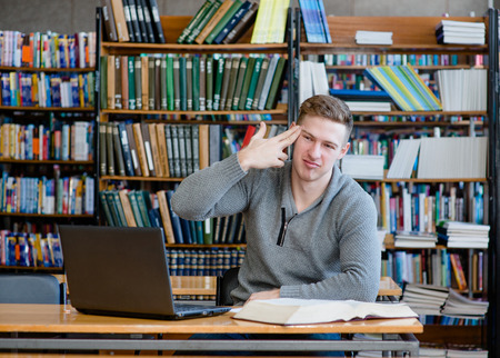 college boy: tired  student in library showing gesture suicide