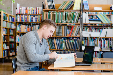 Male student with laptop reading book in the university library photo
