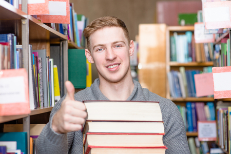 tutorials: student with pile books showing thumbs up in college library Stock Photo