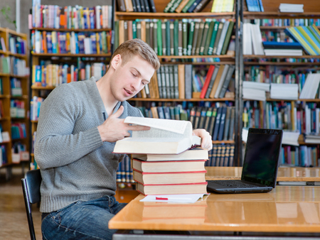 Young male student reading book in library photo