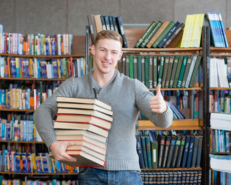 pile of books: student with pile books showing thumbs up in college library Stock Photo