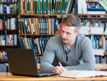 estudiante: Estudiante masculino con el estudio port�til en la biblioteca de la universidad
