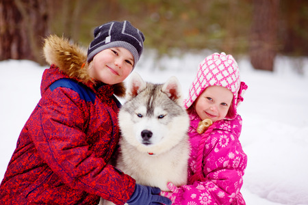 Happy kids embracing hasky dog in winter park photo