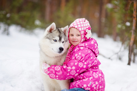 little girl and hasky dog together in winter park photo