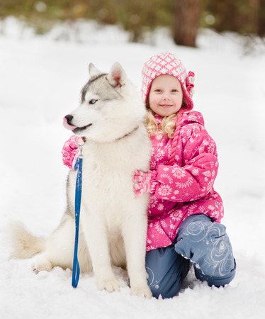 little girl embracing hasky dog in winter park photo