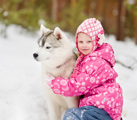 kid embracing hasky dog in winter park photo