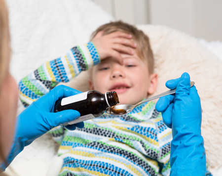 child to the doctor: Sick little boy awaits her medication pouring in a spoon in the foreground