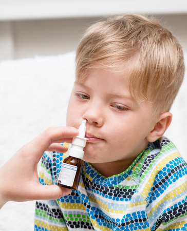 nasal drops: Mother using nose spray to cure her little boy