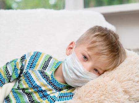 ill little boy in medicine healthcare mask lying on bed Standard-Bild