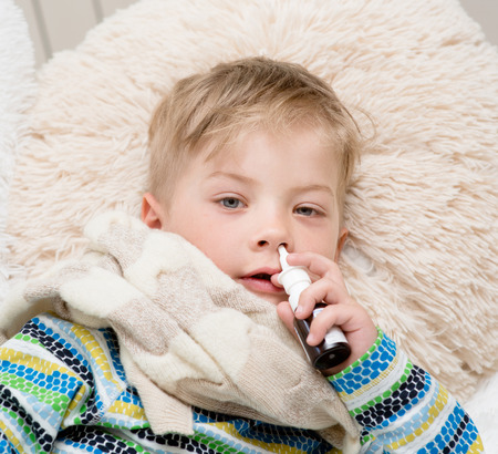 rheum: ill boy with flu at home using nose spray Stock Photo