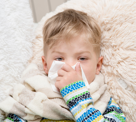 toser: El niño pequeño que sopla su nariz Foto de archivo