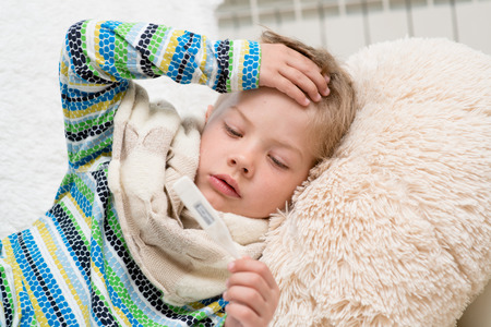 Sick boy with thermometer laying in bed and taking temperature Stock Photo