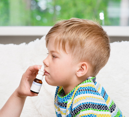 nasal drops: Mother using nose spray to cure her little boy. Focus on hand Stock Photo