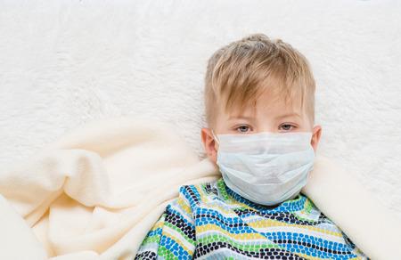 ill little boy in medicine healthcare mask