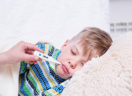 niños enfermos: Muchacho enfermo acostado en la cama con un termómetro en la boca Foto de archivo