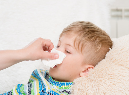 mother wipes her nose son Stock Photo