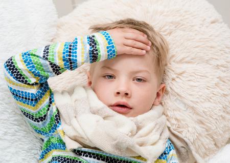 niños enfermos: Muchacho enfermo que pone en cama y tomar la temperatura