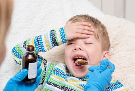 jarabe: Niño pequeño que toma la medicina con una cuchara.