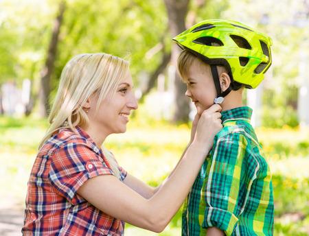 mama e hijo: joven madre viste a su casco de bicicleta hijo Foto de archivo