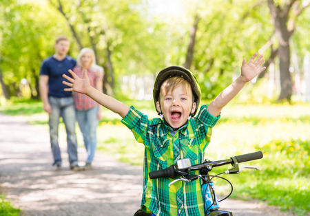 ride: joyful child on a bicycle with his parents in the park Stock Photo